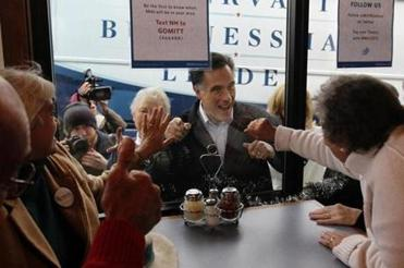 Mitt Romney waved to voters inside Village Pizza in Newport, N.H., yesterday.